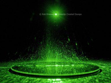opspattend zand in groen laserlicht
